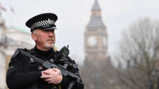 An armed police officer patrols by a security cordon set up along Whitehall by the Houses of Parliament on March 23, 2017 in London.